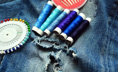 Photo for Close up picture of ripped denim textile with sewing tools. DIY concept - Royalty Free Image