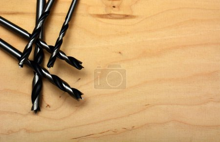 Photo for Close up shot of twist drilling tools on a wooden surface. DIY concept - Royalty Free Image