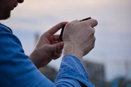 Photo pour Image rapprochée des mains d'un homme avec un smartphone. Fond flou - image libre de droit