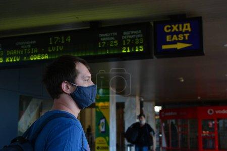 Photo pour Kiev, Ukraine - 21 juillet 2020 : Éclosion de coronavirus à Kiev, la capitale de l'Ukraine : les passagers marchent le long de la gare centrale avec des masques protecteurs. Homme en masque noir. - image libre de droit