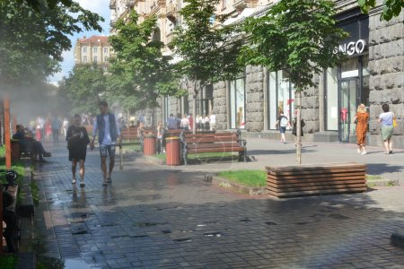 Photo pour Kiev, Ukraine - 17 juillet 2020 : Système de refroidissement sur la rue Khreschatyk, pulvérisant une vapeur froide. Les gens marchent dans la rue. - image libre de droit