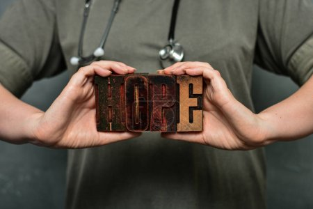 """Photo for A medical worker with a stethoscope holds the word """"hope"""" made of wooden typographic letters. Health care staff, doctor, nurse, high quality medical care concept. - Royalty Free Image"""