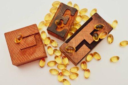 Photo pour Capsules de gel mou de vitamine E et lettre typographique en bois E. Concept de soutien des soins de santé et de l'immunité. - image libre de droit