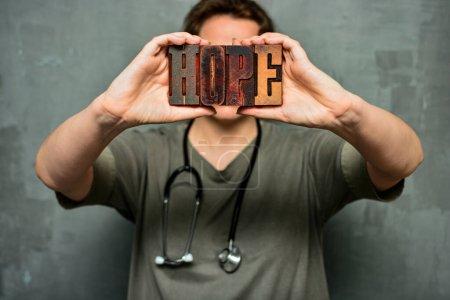 """Photo pour Un travailleur médical muni d'un stéthoscope porte le mot """"espoir"""" fait de lettres typographiques en bois. Personnel de santé, médecin, infirmière, concept de soins médicaux de haute qualité. - image libre de droit"""