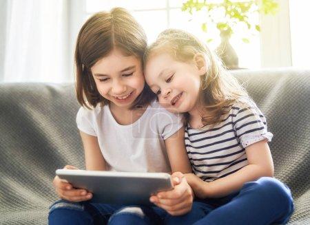 Lindos niños pequeños están jugando con la tableta. Chicas felices en casa. Divertidas hermanas encantadoras se divierten en la habitación de los niños .