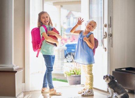 Alumnos de escuela primaria. Chicas con mochila es ir a la escuela desde su casa. Inicio de clases. Primer día de otoño