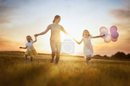 Photo for Happy loving family is having fun on nature in the summer. Young mother and two daughters are laughing and playing on meadow at sunset background. - Royalty Free Image