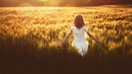 Photo for Happy kid is having fun on nature in the summer. Child is playing on meadow at sunset background. Girl is running on cereal field and touching wheat ears. - Royalty Free Image