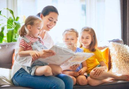 Photo pour Heureuse famille aimante. jolie jeune mère lisant un livre à ses filles - image libre de droit