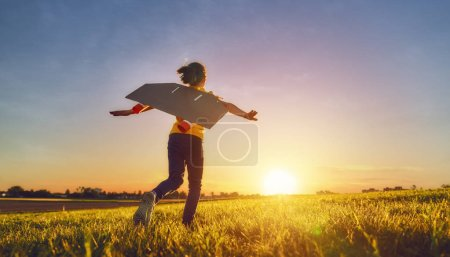 Little girl playing astronaut. Child fleeing on the background of sunset sky. Kid dreaming of becoming a spaceman.