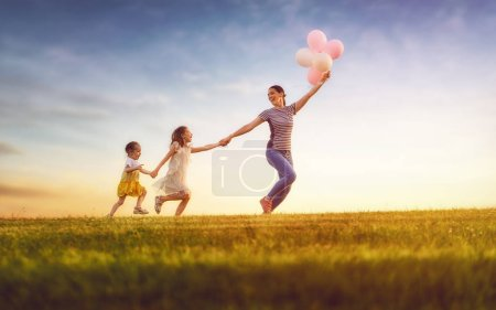Happy loving family is having fun on nature in the summer. Young mother and two daughters are laughing and playing on meadow at sunset background.