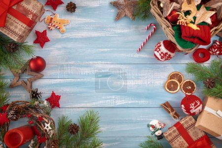 Photo for Merry Christmas and Happy Holidays! Baubles with ornaments and gift boxes on wooden desk. Top view. Xmas traditions. Space for your text. - Royalty Free Image