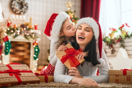 Photo pour Joyeux Noël et Joyeuses Fêtes ! Joyeux maman et ses filles mignonnes filles échanger des cadeaux. Parent et petits enfants s'amusent près de l'arbre à l'intérieur. Famille aimante avec des cadeaux dans la chambre . - image libre de droit