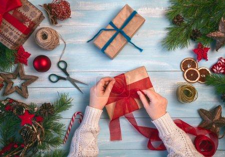Foto de ¡Feliz Navidad y felices fiestas! Una mujer prepara los regalos de Navidad. Chucherías, presenta, caramelo con adornos. Vista superior. Tradiciones familiares - Imagen libre de derechos