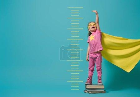 Foto de Un niño jugando a ser superhéroe. El niño mide el crecimiento en el fondo de la pared azul brillante. Concepto de poder femenino. Colores amarillo, rosa y turquesa . - Imagen libre de derechos