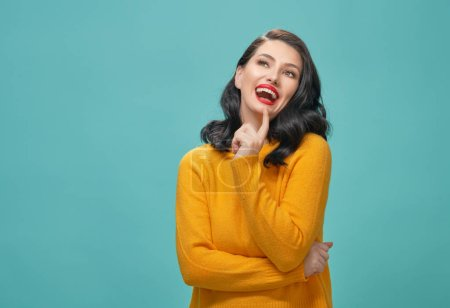 Photo for Joyful beautiful young woman in yellow sweater posing on turquoise background. - Royalty Free Image