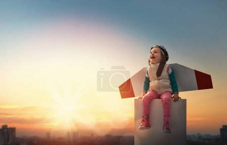 Photo for Little child playing pilot. Girl on the background of sunset sky. Kid in an astronaut costume dreaming of becoming a spaceman. - Royalty Free Image
