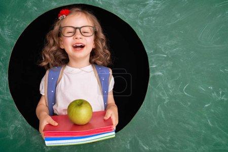 Photo pour Retourne à l'école ! Joyeux enfant industrieux mignon à l'intérieur. Enfant en classe sur fond de tableau . - image libre de droit