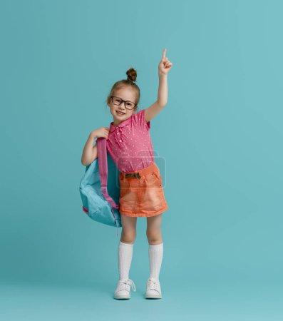 Photo pour Retourner à l'école et passer du bon temps ! Mignon enfant industrieux sur fond de mur en papier couleur. Enfant avec sac à dos. Fille prête à étudier. - image libre de droit