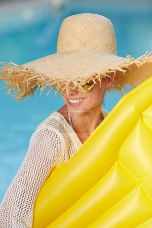 Photo for Young happy woman relaxing in a swimming pool - Royalty Free Image