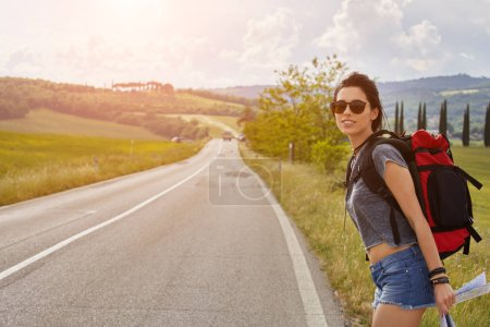 Photo for Beautiful traveler woman carrying backpack walking on country road. - Royalty Free Image