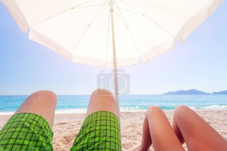 legs of two peoples under umbrella on beach