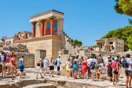 Photo pour HERAKLION, CRETE, GRÈCE - 27 JUILLET 2011 : Groupe touristique en visite guidée au palais Knossos près de l'entrée nord restaurée avec fresque de taureau chargée - image libre de droit