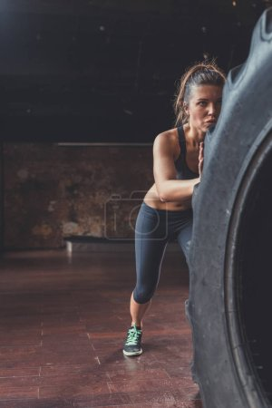 Photo for Young athletic woman with a crossfit wheel in the loft - Royalty Free Image