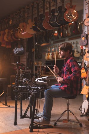 Photo for Young musician playing the drums in a music store - Royalty Free Image