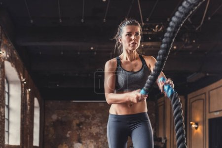 Young girl with a rope on a cross-training in the loft