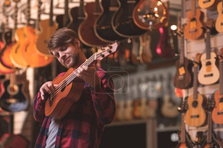 A young musician playing the ukulele in a music store