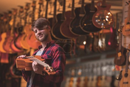 Smiling musician with a ukulele in a music store