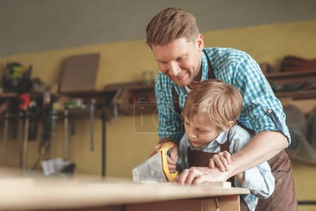Photo for Father and son sawing a board in the carpentry - Royalty Free Image