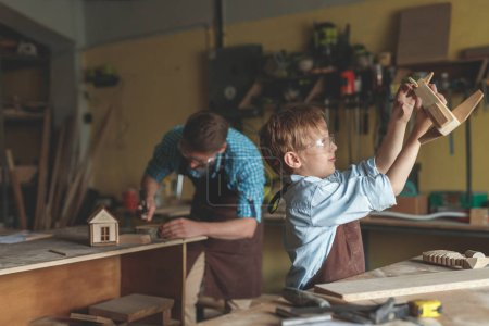 Young master and a little boy in the carpentry