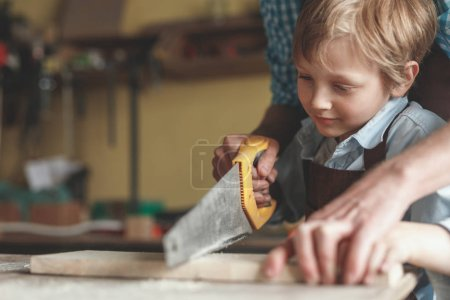 Little boy sawing a plank in carpentry