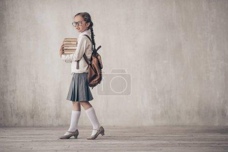 Photo pour Petite fille avec des livres en studio - image libre de droit