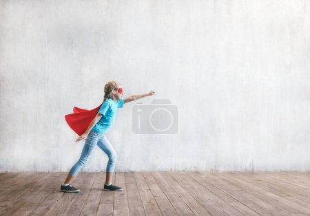 Flying little super hero in studio