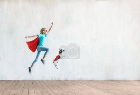 Jumping little child with a dog indoors