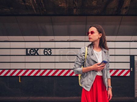 Attractive girl with a phone at a subway station in New York