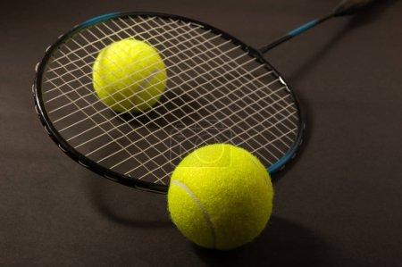 Photo pour Balle de tennis et raquettes sur fond foncé - image libre de droit