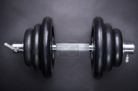 Photo for Dumbbell with typesetting discs weighting on dark background - Royalty Free Image