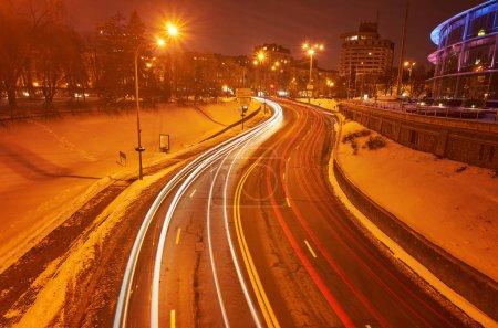 Winterautobahn in der Nacht mit Lampen beleuchtet