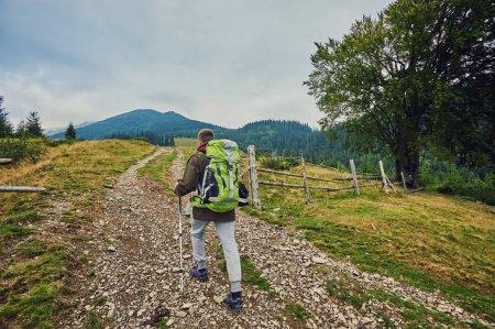 Photo pour Homme randonnée au coucher du soleil montagnes avec sac à dos lourd Voyage Lifestyle wanderlust aventure concept vacances d'été en plein air seul dans la nature - image libre de droit