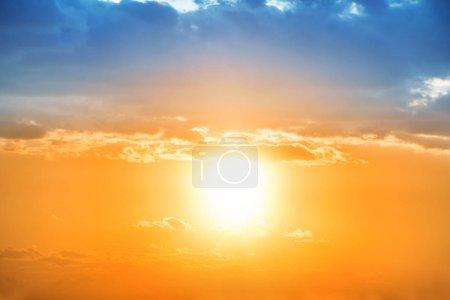 Photo pour Coucher de soleil dans le ciel orange avec grand soleil et nuage bleu - image libre de droit