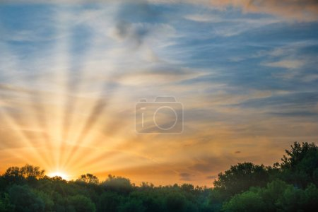 Photo for Sunset over forest silhouette. Dramatic sky with sun rays and clouds - Royalty Free Image