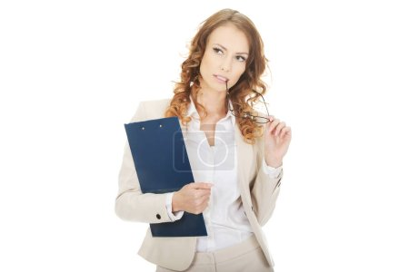 Photo for Thoughtful businesswoman holding a clipboard. - Royalty Free Image