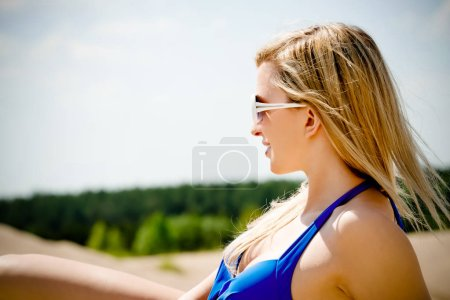 Photo for Happy woman sitting in beach and enjoying summer vacation. - Royalty Free Image