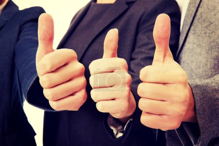 Three business people showing thumbs up