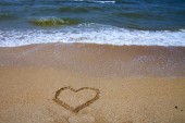 Beautiful beach and sea surf. Summer seascape. Heart in the sand and wave close up.