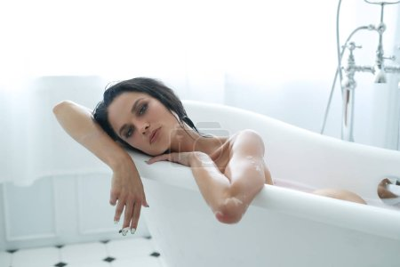 gorgeous young woman lying in bathtub